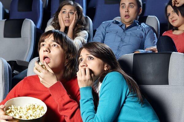 Gente pasando miedo en una sala de cine