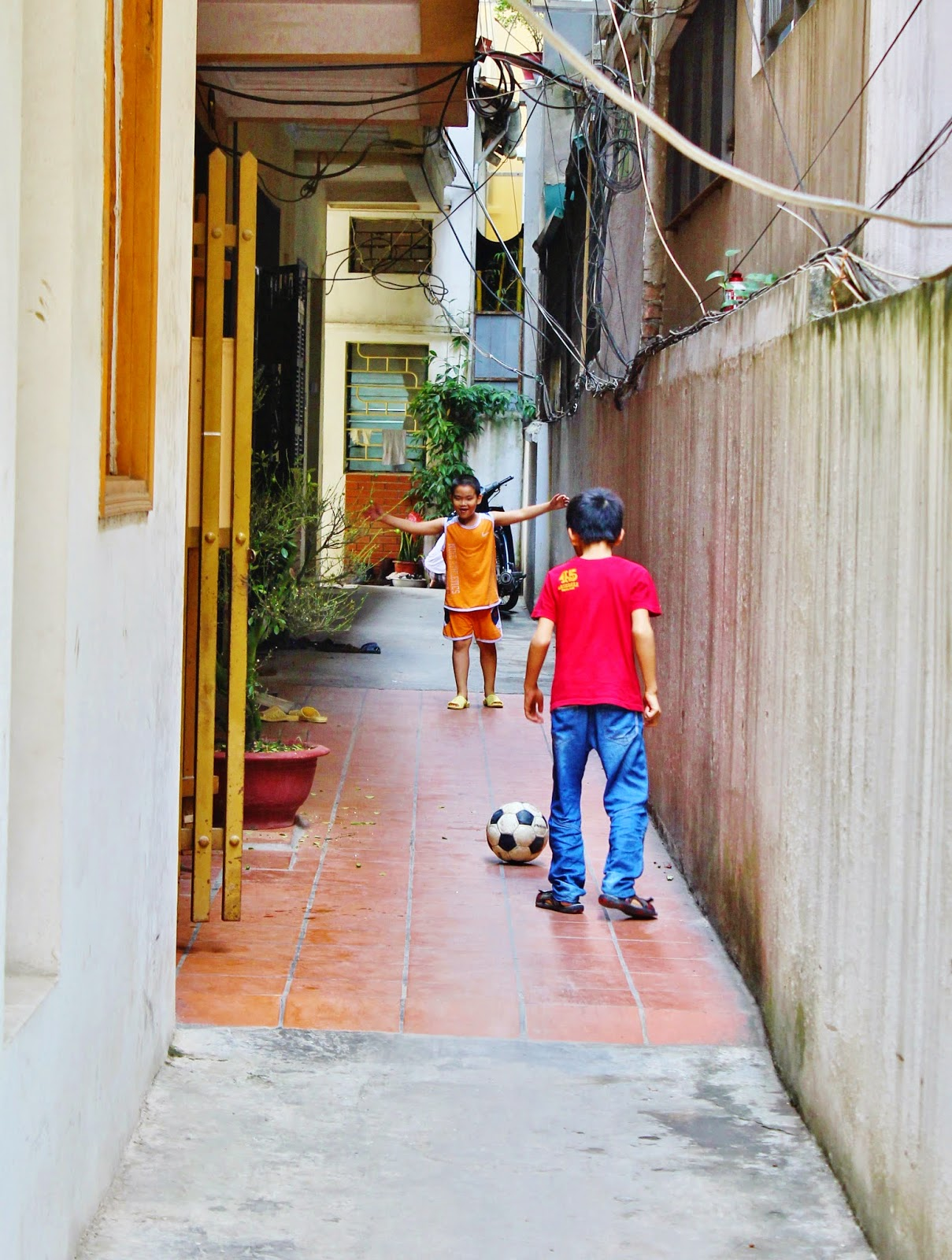 0dda9022fdd Random Vietnamese kids kicking around a soccer ball on the backstreets of  Hanoi.