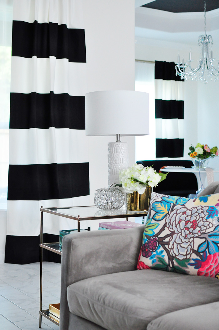 Black and white striped curtains in an open concept living and dining space with chinoiserie decor touches. | via monicawantsit.com