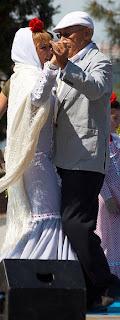 Una pareja en un baile típico vestidos con el traje típico de Madrid, el de chulapos con gorra y chaquetilla y el de chulapas con vestido largo y mantón de Manila