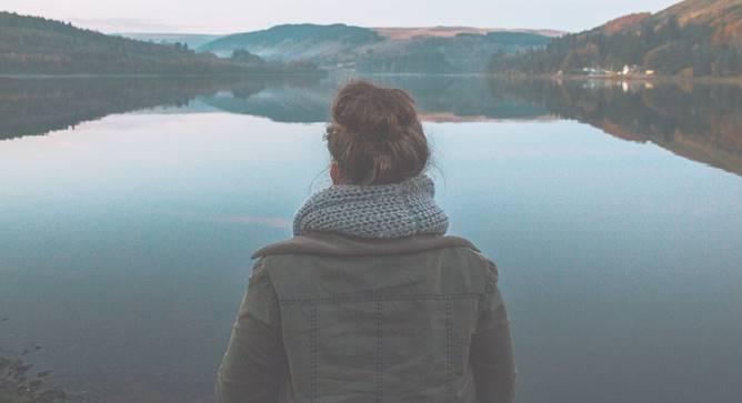 wanita menikmati keindahan danau