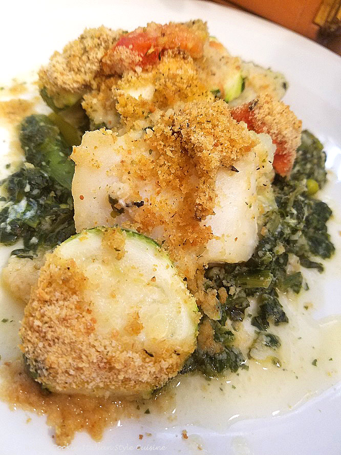 This is a baked cod fish on a white plate with a fall orange leaf basket in the background, a blue water glass and fork with napkin. The plate has a bed of spinach topped with baked cod fish with roasted vegetables on top along with bread crumbs toasted with Parmesan cheese and sliced tomatoes.