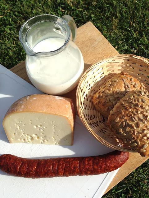 Een glazen kannetje geitenmelk, een stuk kaas, een worst en een mandje met broodjes