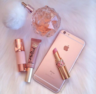 A flat lay photo with rose gold accessories, including perfume bottle, lipgloss, and rose gold iphone 7
