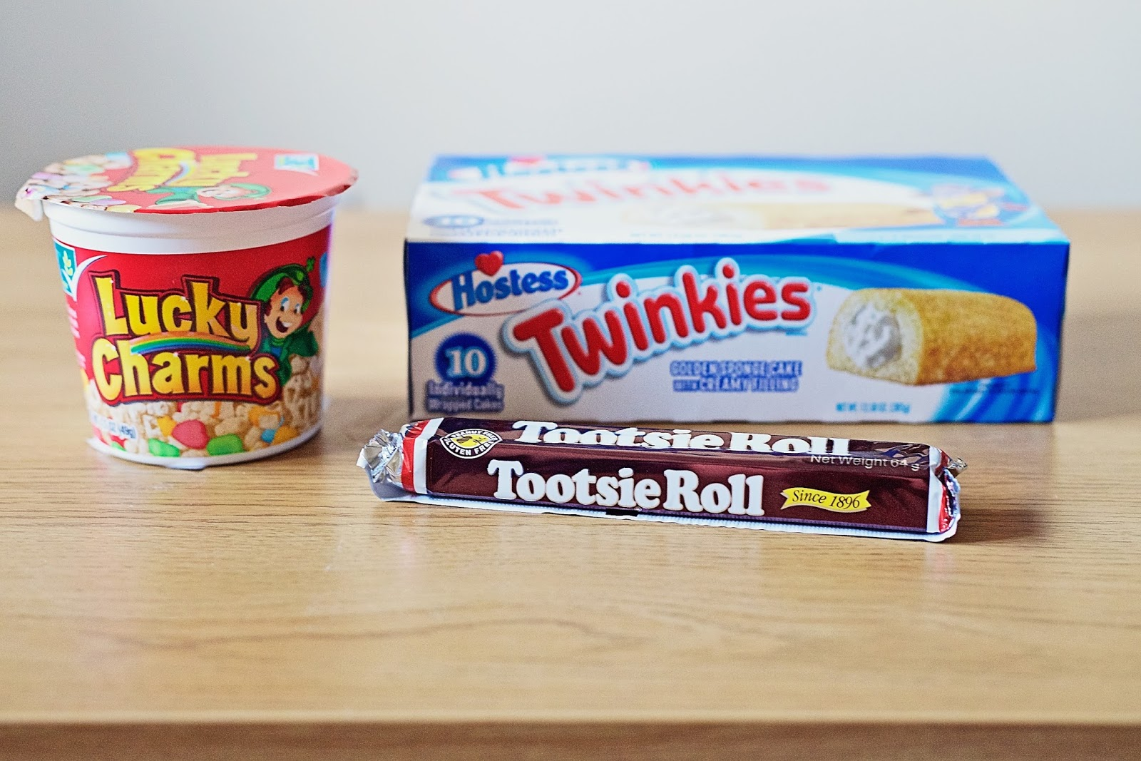 Box of twinkles, lucky charms cereal and a tootsie roll