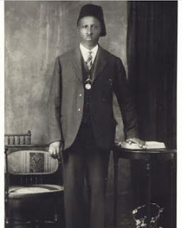 Noble Drew Ali standing in masonic stance wearing a suit and tie with a black fez on top of his head.