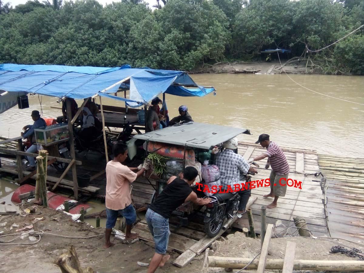 Warga menggunakan getek untuk menyeberangi sungai.
