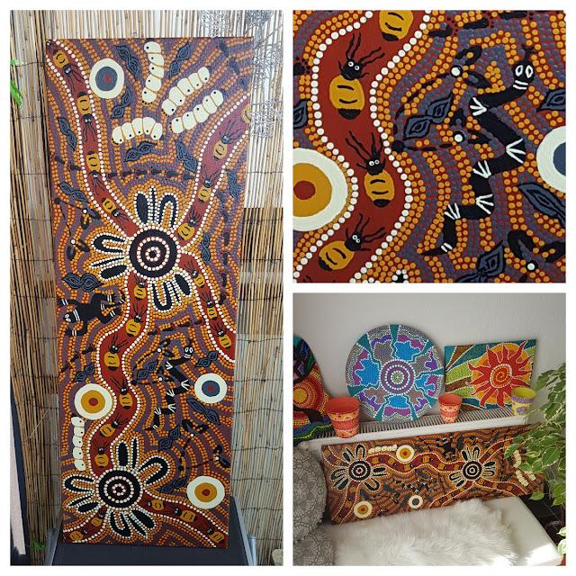 """Das Bild """"Bushtucker"""" von Elke Wolf wird in dieser Collage zeigt. In der nahaufnahme sind gemalte Käfer und eine Schlange zu erkennen. Das Bild besteht aus Punkten und Symbolen in Naturfarben und wurde mit vielen Punkten gemalt."""