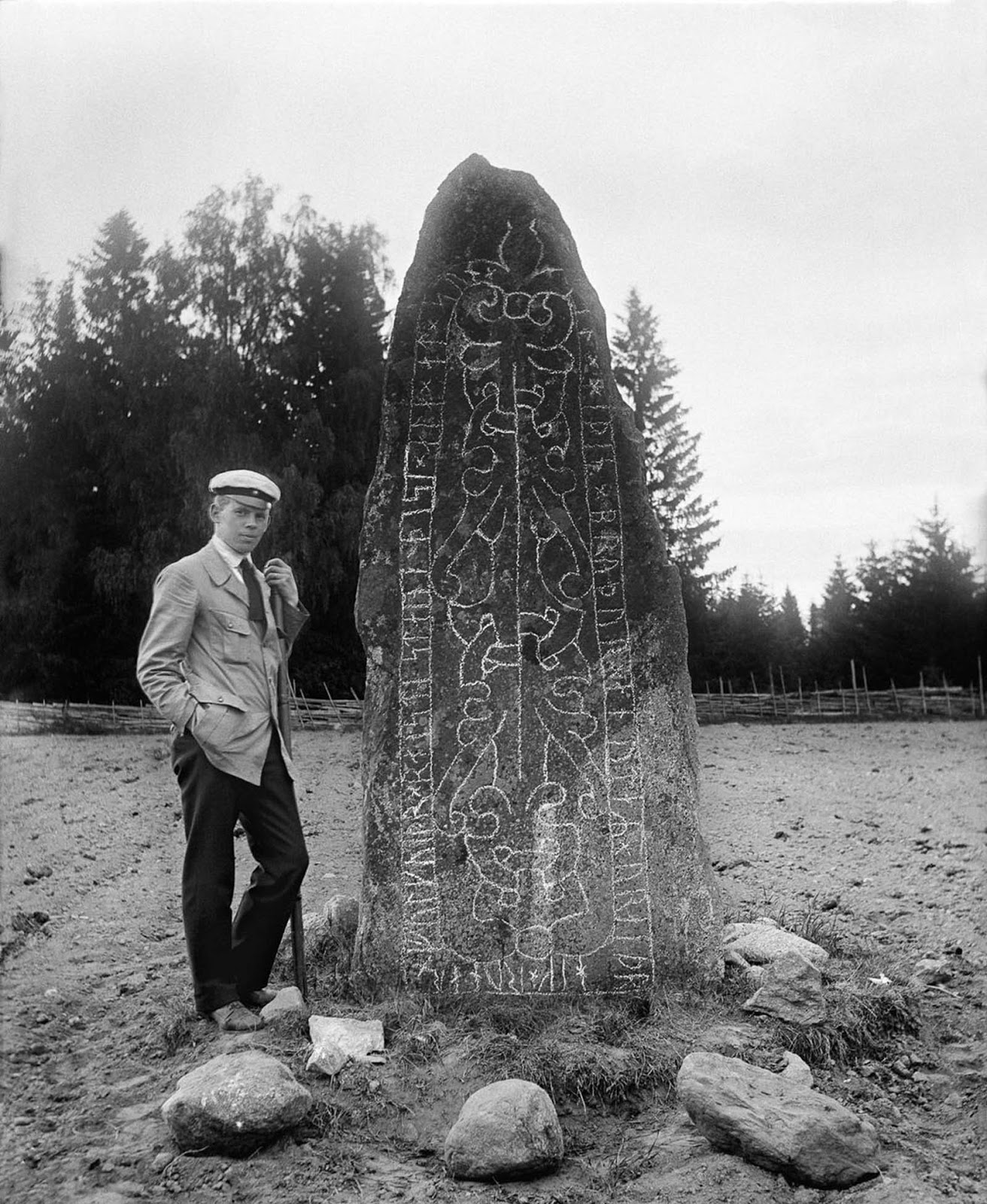A student with a runestone in the Anundshög prehistoric area in Badelunda. The inscription reads,