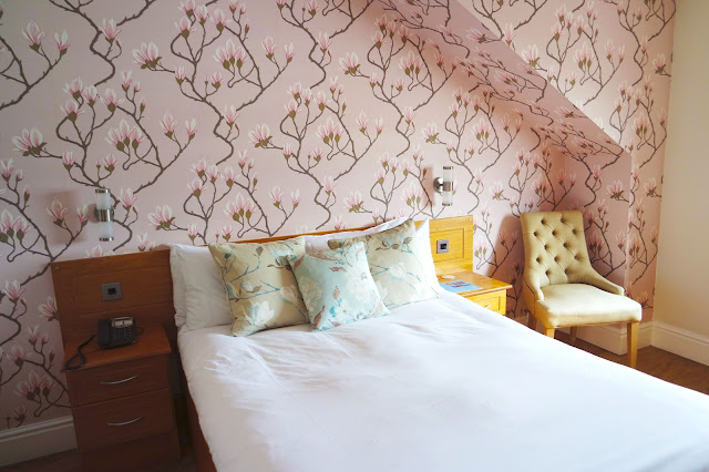 hotel room with pink orchid print wallpaper and white bedding
