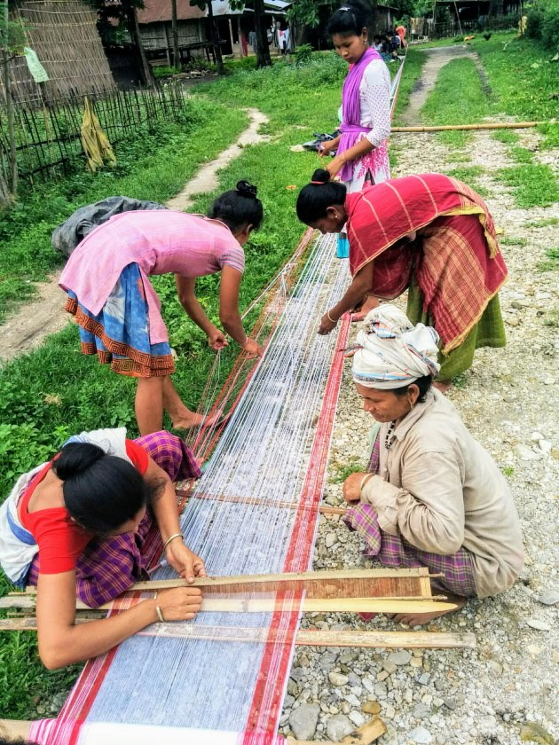 Mishing tribal women setting the threads right for the looms
