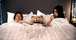 Ted, from the film of the same name, in bed with Mark Wahlberg & Mila Kunis