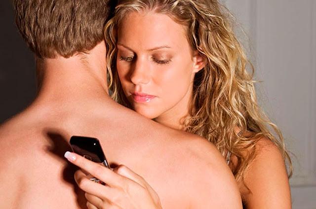 Mujer abrazando a su novio mientras revisa su celular