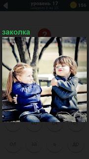 На скамейке сидят мальчик и девочка, руками обнимая себя и заколка в волосах девочки