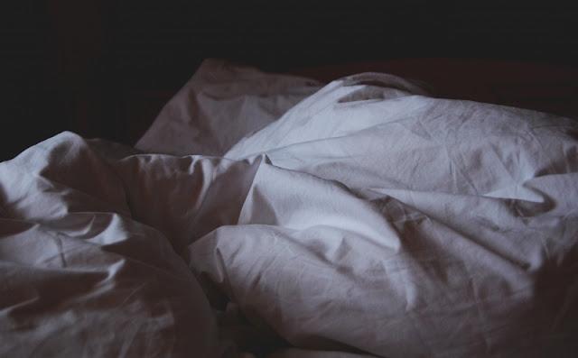 Fotografía de una cama deshecha en una habitación con poca luz.