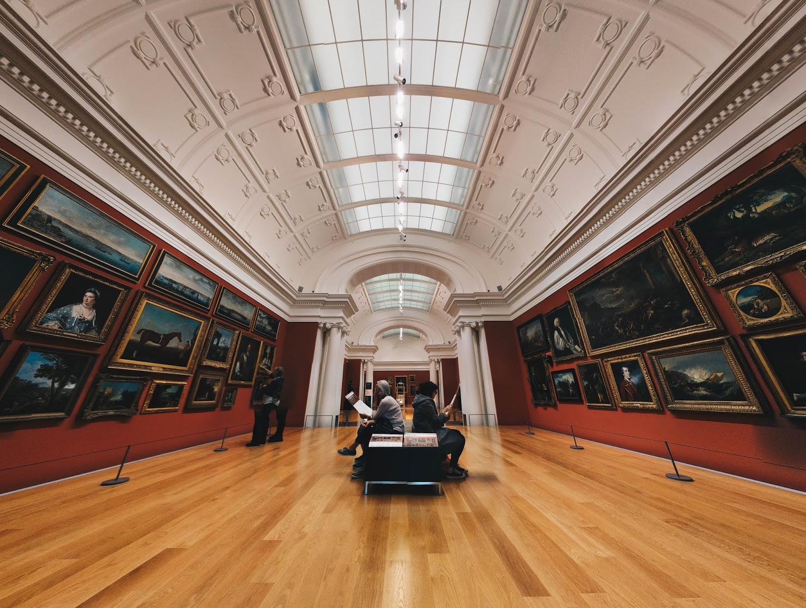 A photo looking down a room in an art gallery with paintings on the walls on either side, with a bench in the middle with people sitting and sketching, and two people looking at the paintings on the left - photo taken in Auckland Art Gallery Toi o Tāmaki, Auckland, New Zealand