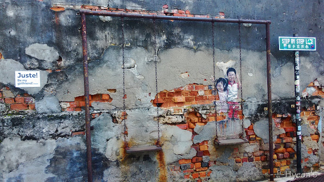children on swing street art penang