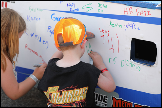 A young fan signs Craig Kruckeberg's #55 truck 'Tonk' prior to the Bandit Series event at Cedar Rapids on Saturday, June 9th