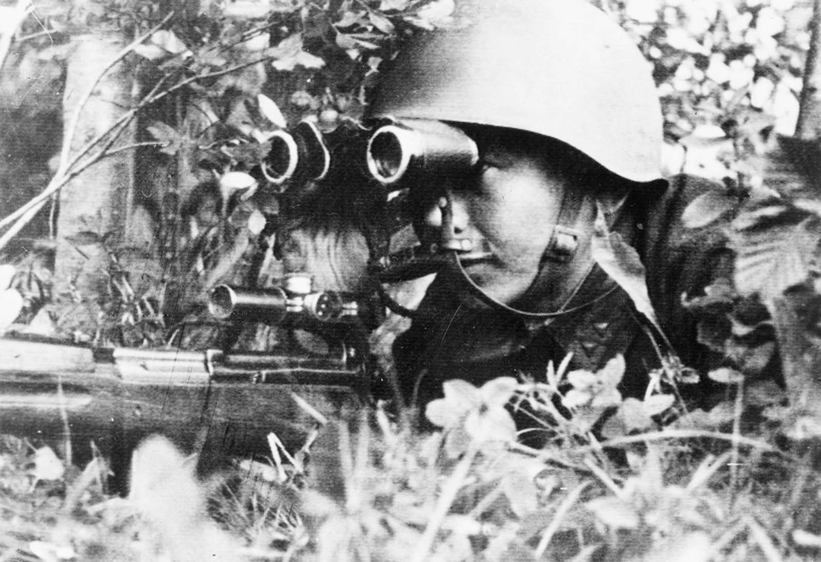 Sergeant P. Dorzhiev, a Russian sniper who killed 181 Germans on the Leningrad front, looking through binoculars, and holding a rifle, sometime in 1942.