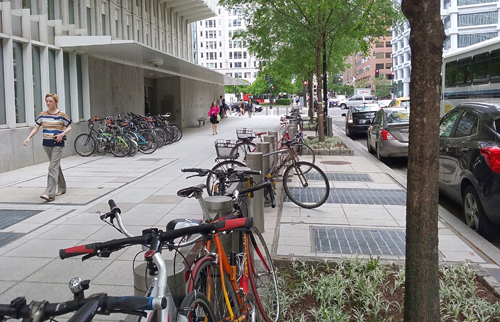 Bikes lined up on sidewalk by building