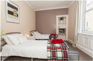Image of bed with tartan blanket