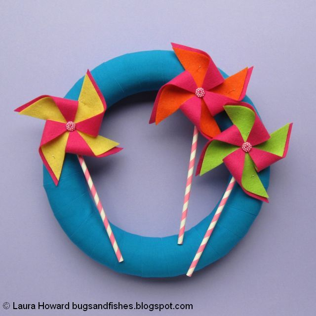 fabric-wrapped wreath decorated with pinwheels made from felt, buttons and paper straws