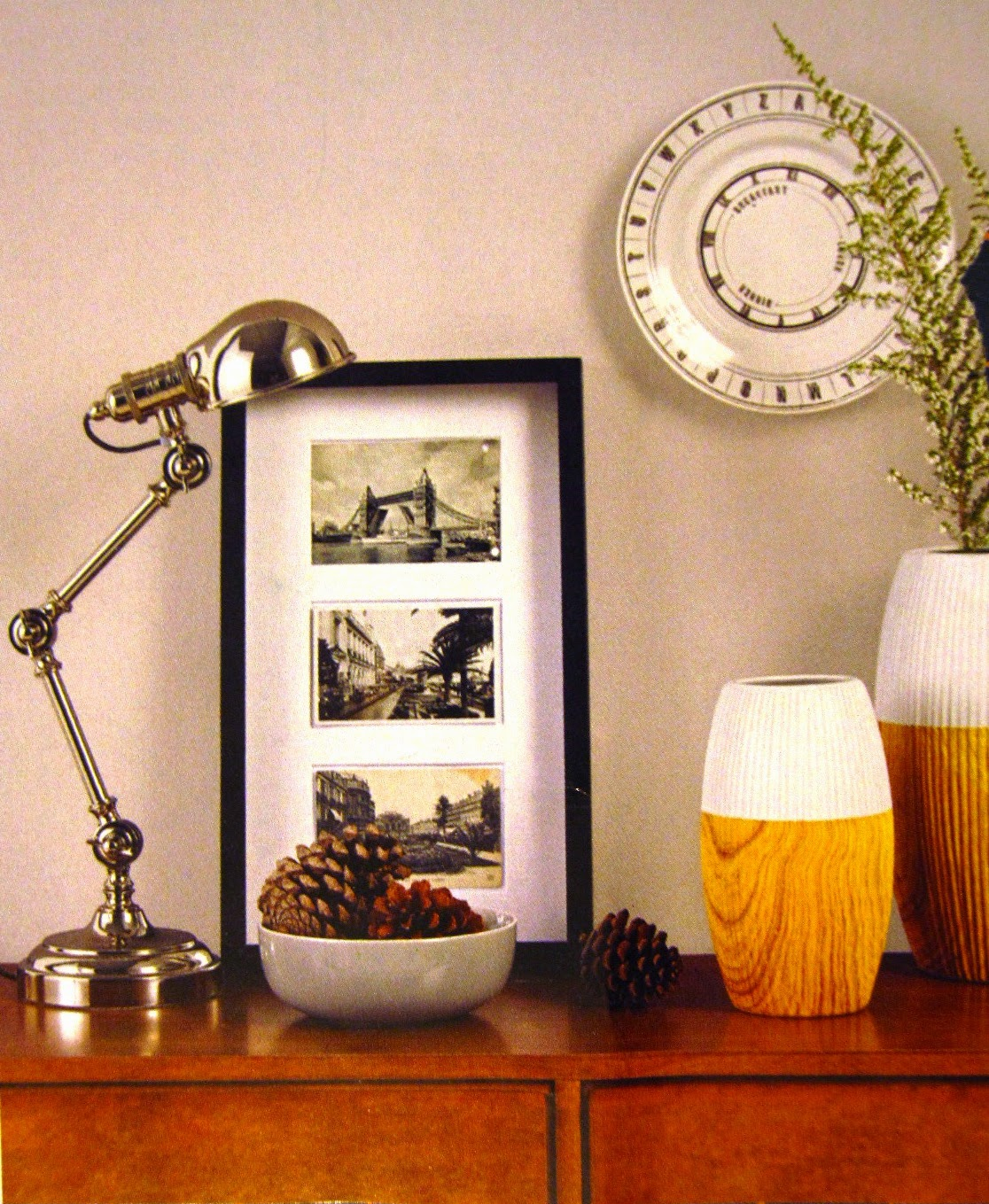 Catalogue ad showing a silver lamp, a bowl of pinecones, a three-section picture, two wooden vases (dip-painted white, one with a sprig of bush), and a decorator plate on the wall.