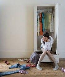 Mujer decidiendo vestimenta. Armario abierto y ropa desperdigada