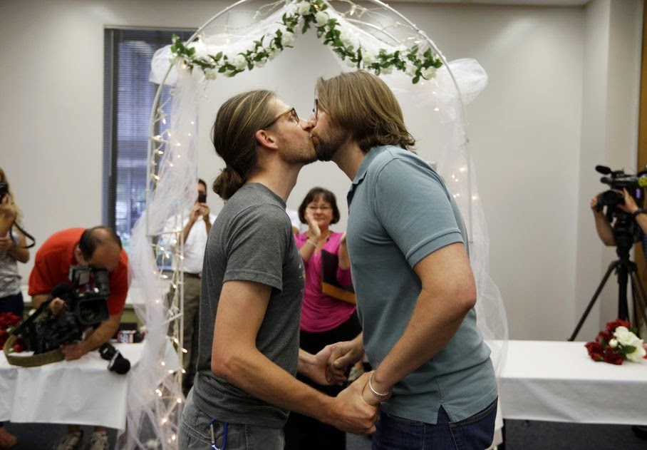 Jake Miller and Craig Bowen, right, kiss after being married by Marion County Clerk Beth White, center, in Indianapolis, Wednesday, June 25, 2014. A federal judge struck down Indiana's ban on same-sex marriage Wednesday in a ruling that immediately allowed gay couples to wed.