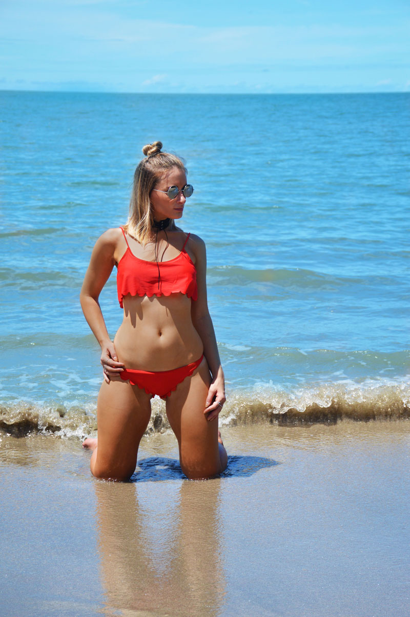 tanned blonde girl in red scallop edge bikini on tropical four mile beach port douglas australia