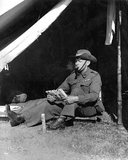 Photograph of a soldier reading in a tent