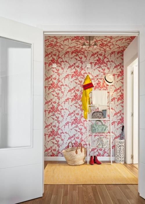 papel pintado de flores rjoas con escalera, cestas y alfombra en recibidor chicanddeco