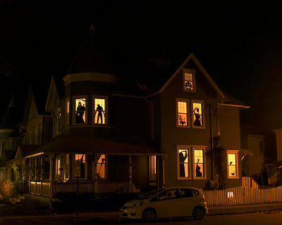 house at night with spooky Halloween silhouettes in windows