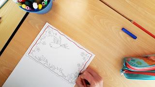 Uma mão a pintar um postal com desenhos inspirados nos lenços dos namorados portugueses