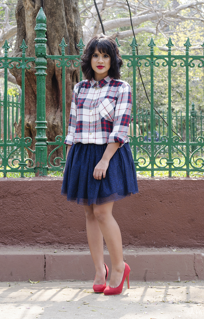 Image of style blogger wearing a plaid checked shirt, tutu skirt, red high heels with a mini bag, red lips and a wavy bob hairstyle