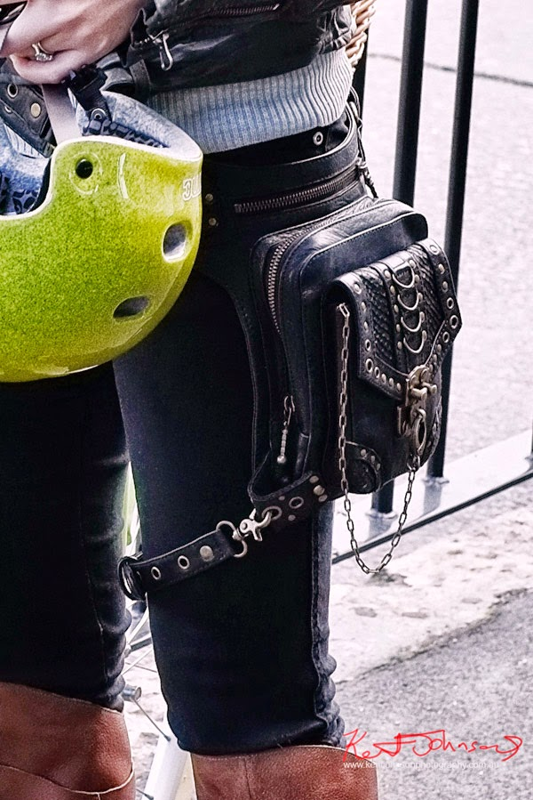Detail, belted chained and tooled, strapped-black-bag slung on waist with tie-down, Photo by Kent Johnson.
