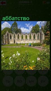 стоят стены старинного аббатства, впереди зеленая лужайка