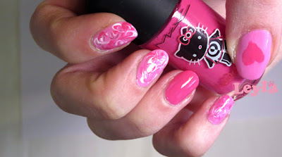 cute valentine's nail art look with hello kitty polish, swirl marble nails and hearts in pink and white