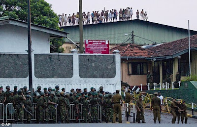 Rioting inmates on the roof of Colombo's Welikoda prison