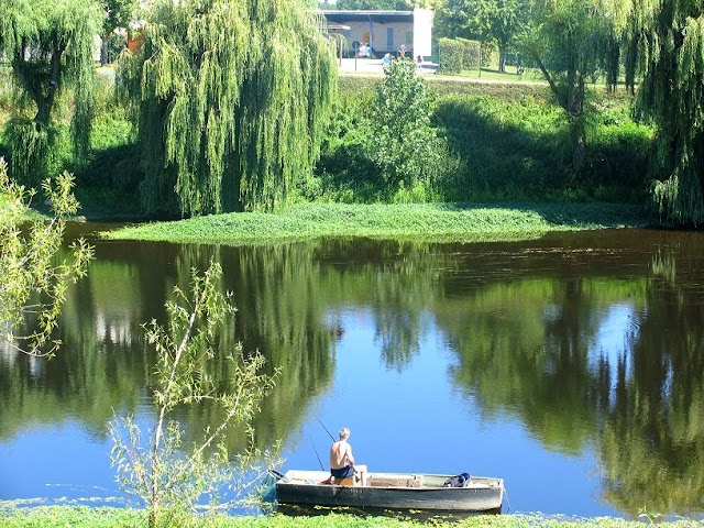 man fishing from a boat on the river Vienne at L'Île-Bouchard