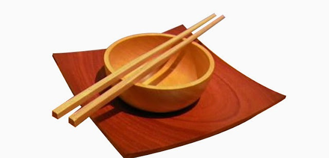 Palillos chinos de madera sobre tazón