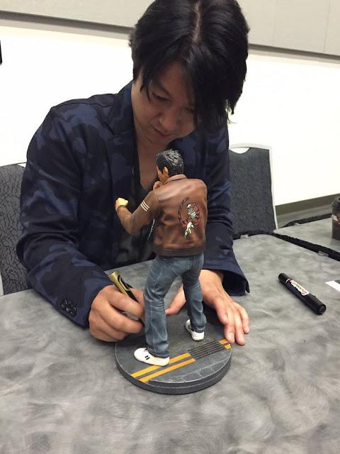 Masaya Matsukaze signing a Ryo Hazuki figurine