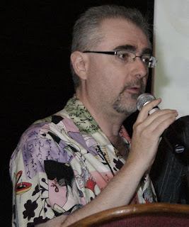 Robin Laws, an older gentleman with short grey hair, a thin goatee and moustache, and black glasses, wearing a colourful shirt, speaking into a microphone.