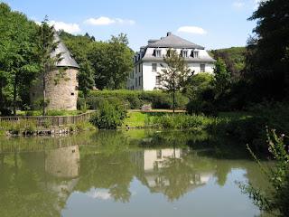 Ein weißes Haus steht an einem See. Daneben steht ein brauner, runter Turm mit einem Spitzdach