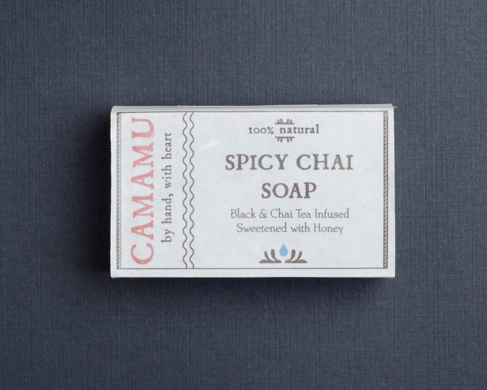 Camamu Spicy Chai Soap in it's packaging arranged as a flatlay on a black background