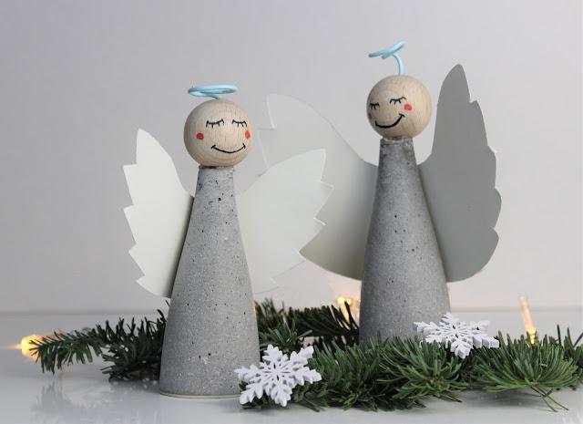 zwei fertig gebastelte Engel aus Beton, mit Papierflügeln und einer bemalten Holzkugel als Kopf.