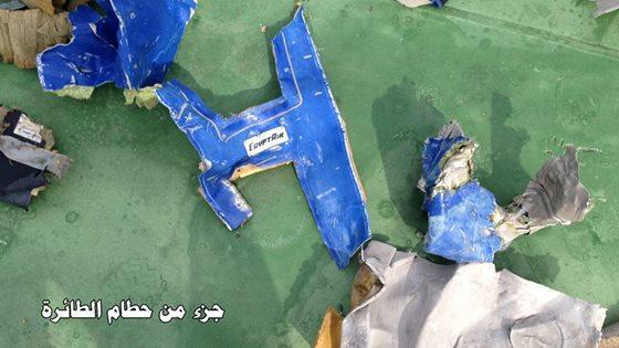 """قطعة ام الطائرة ذات اللون الأزرق ومكتوب عليها شعار شركة """"مصر للطيران"""