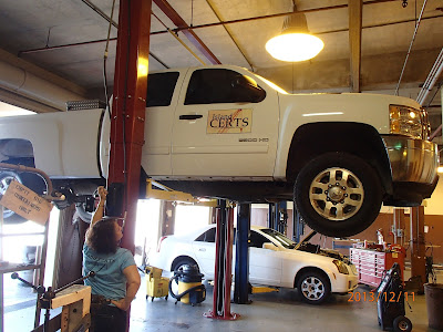 Photo of Nancy Barnhouse pulling a lever to lift a white truck for a vehicle maintenance check