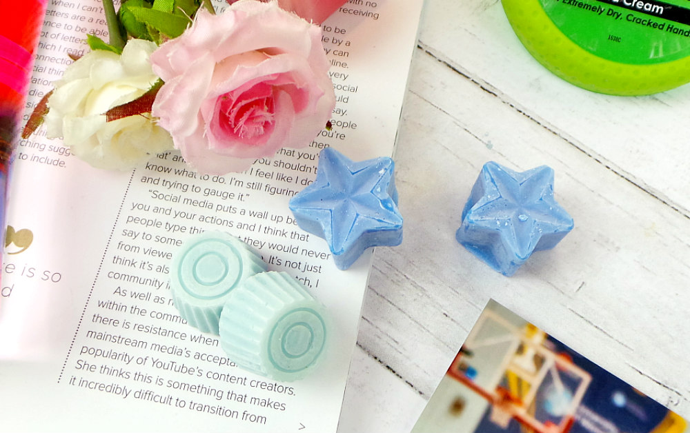 there are 4 wax melts, 2 round light blue ones on the right and 2 star shaped darker blue on the left