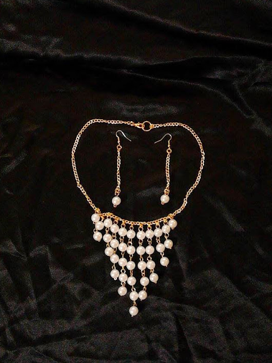 Necklace and earrings with white pearls and gold chain
